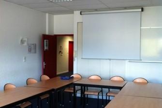 Salle de réunion avec des tables disposés en U et un tableau blanc