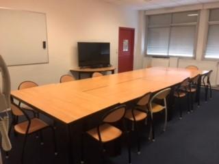 Salle de réunion disposé en rectangle avec écran télé